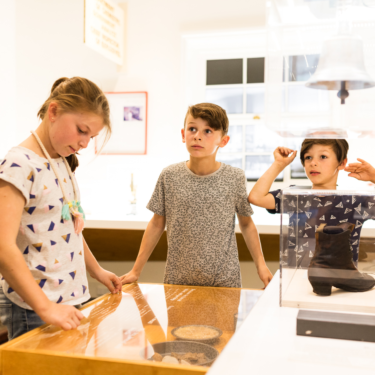 Three young people looking at a museum display