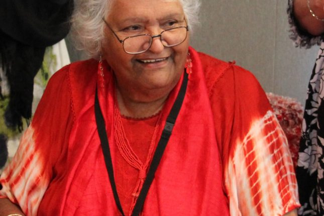 A photograph of Aunty Muriel Van Der Byl sitting at a table holding a copy of the design for the new Australian $50 note.