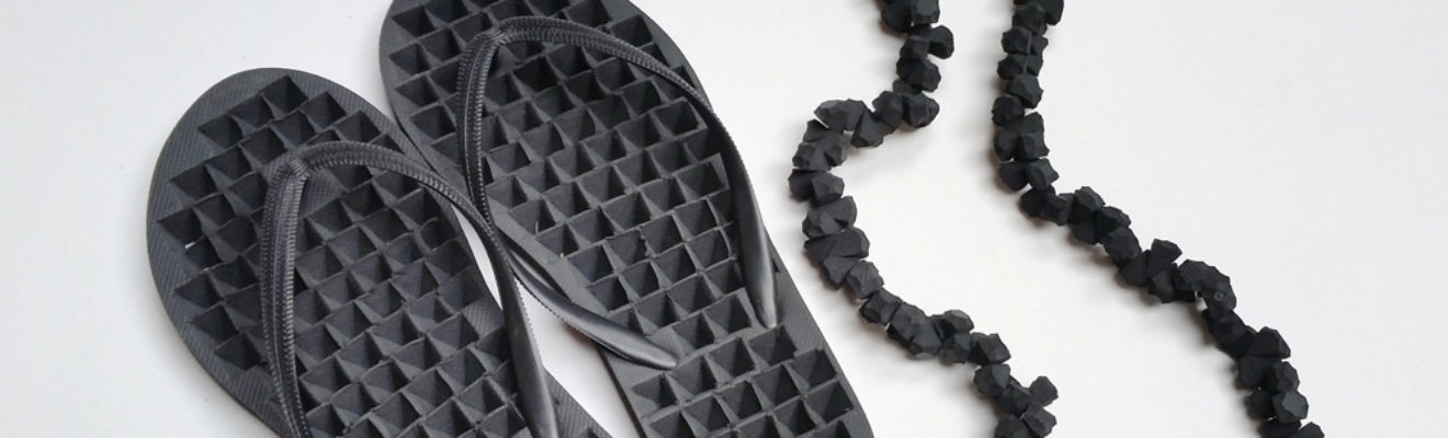 artwork of black thongs and black necklace made from parts of the thongs